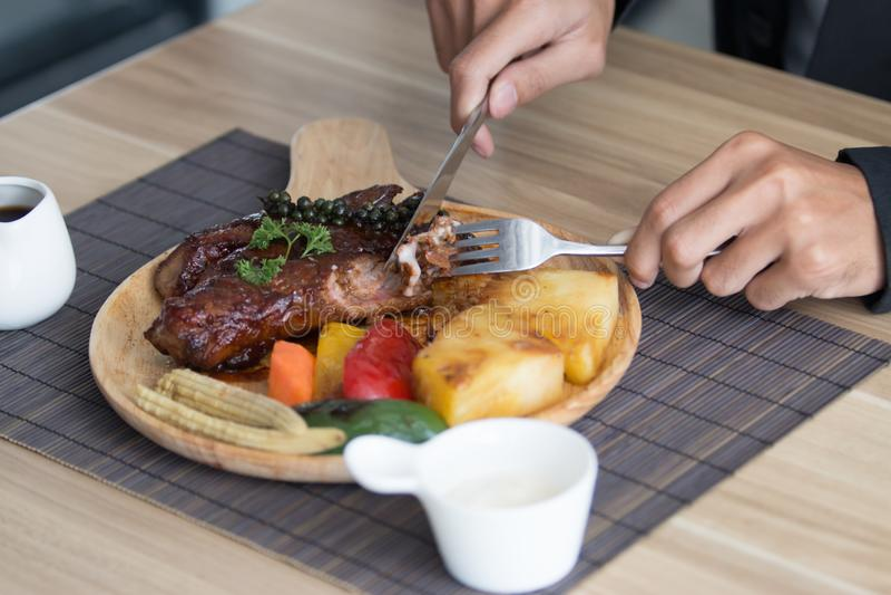 Forcella e coltello della tenuta dell'uomo d'affari che mangiano bistecca fotografie stock libere da diritti