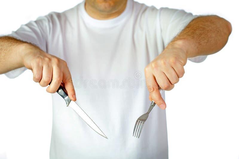 Forcella e coltello in mani fotografia stock libera da diritti