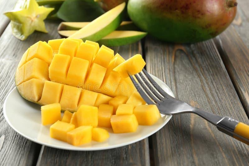 Forcella e piatto con il mango tagliato fresco sulla tavola, primo piano fotografia stock