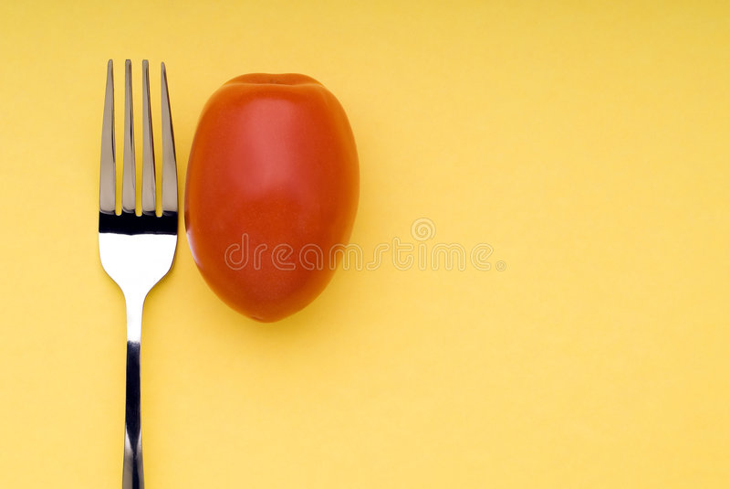 Forcella e pomodoro su colore giallo fotografie stock libere da diritti