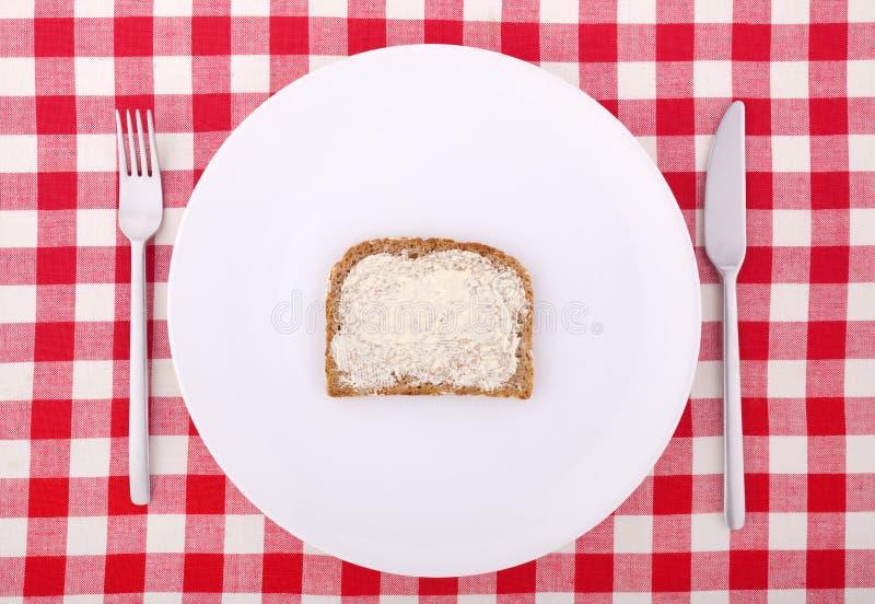 Forcella, lama e una fetta di pane imburrata immagini stock