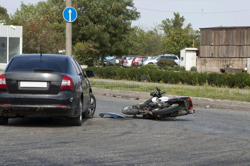 Forcerad motocykel och bil på vägen arkivbild