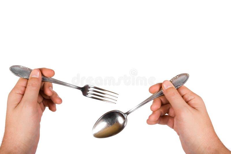 Forchetta e cucchiaio in mani fotografie stock libere da diritti