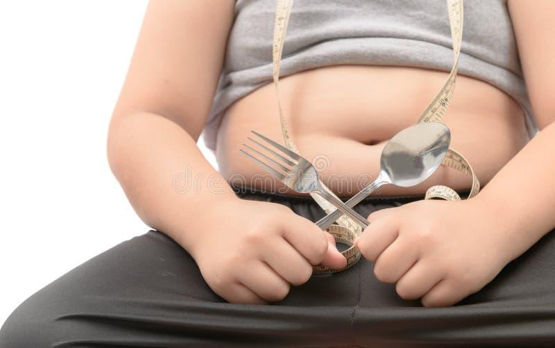 Forchetta obesa e cucchiaio grassi della tenuta del ragazzo isolati fotografia stock libera da diritti