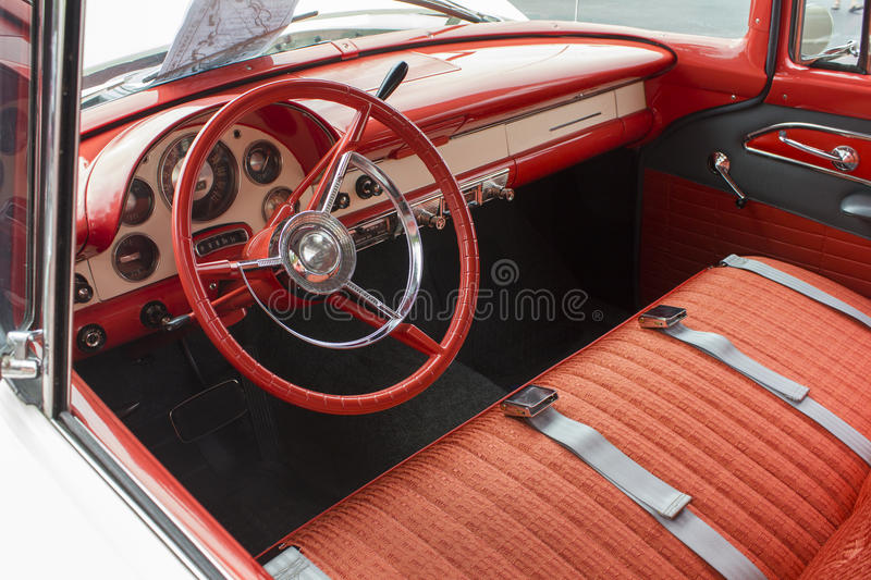 1955 Ford Dash and Interior. 1955 Ford Victoria Dash panel showing the original steering wheel, instruments and trim. Bright red upholstery on the front seat stock image
