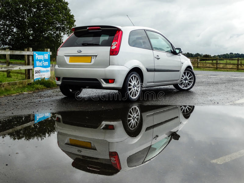 Ford Fiesta MK6 Reflection - Wind Farm. A photo of a MK6 Ford Fiesta featuring a deep reflection from a nearby puddle royalty free stock photos