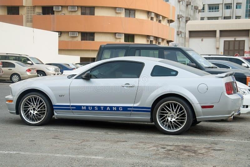 Ford Mustang de plata se coloca en el estacionamiento de la ciudad foto de archivo