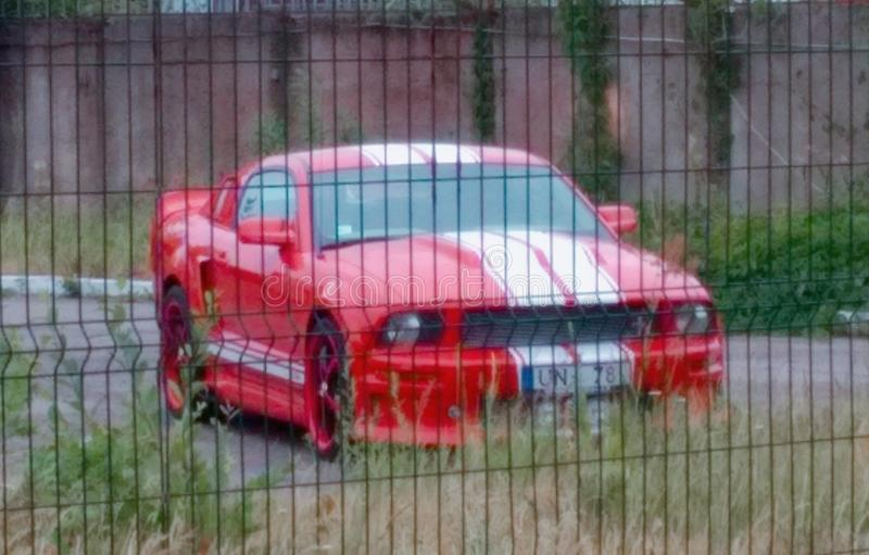 Red body color with blue stripes Ford Mustang on the parking. Red Ford Mustang with white sport racing race stripes on the parking with metal steel security stock images