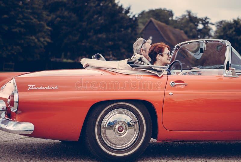 Ζεύγος που οδηγά την κόκκινη Ford Thunderbird κατά τη διάρκεια της ημέρας στοκ εικόνα με δικαίωμα ελεύθερης χρήσης