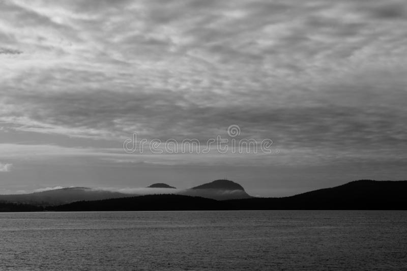 Noire Seascape over Puget Sound Near San Juan Island Washington. Foreboding low clouds and fog adds a air of mystery in the black and white noire image of the royalty free stock photography