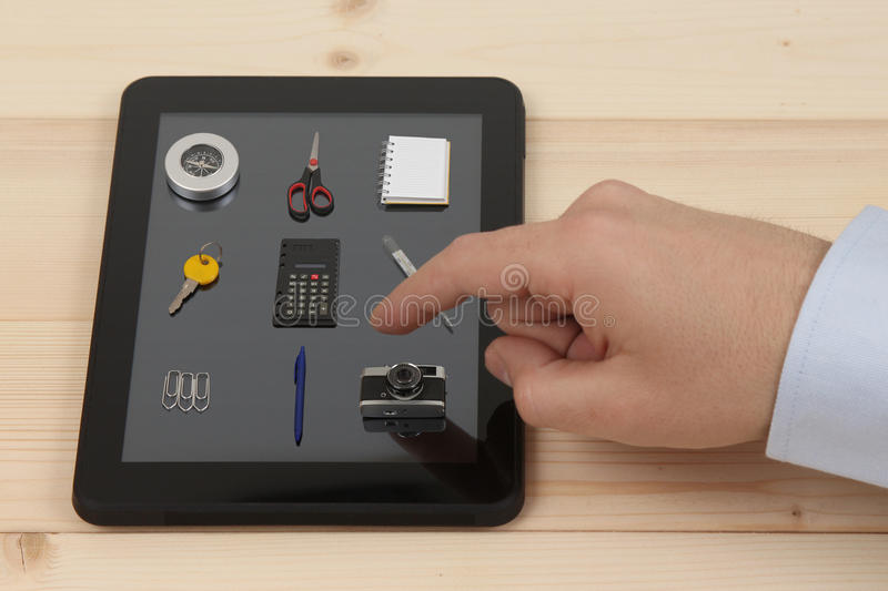 Forefinger pressing the tablet icon with real symbols. Male index finger about to choose one of the options on tablet device with real decreased size objects as stock images
