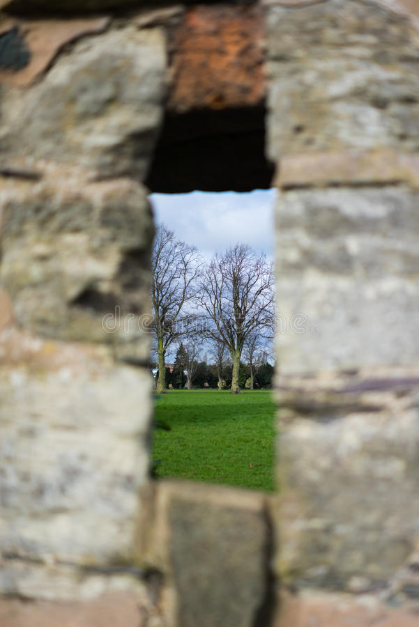Foreground blur background focus. A peek through a stone wall stock photography