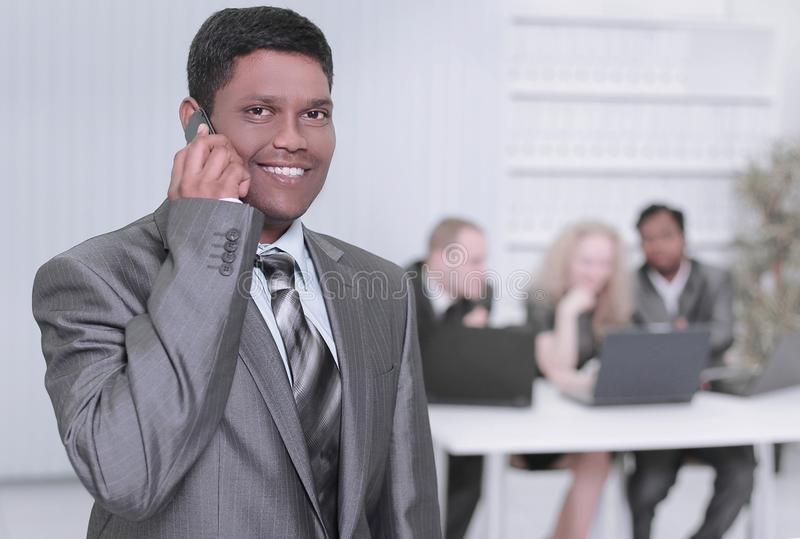 Foreground of a businessman talking on a mobile phone in the office royalty free stock photography