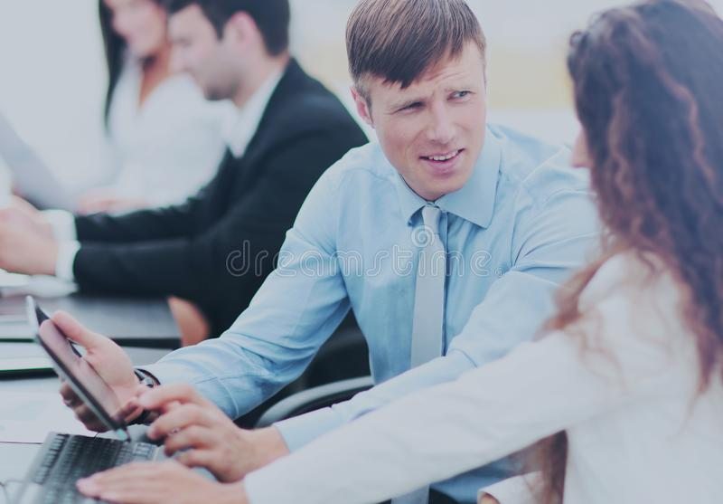 Tax consultant is talking with the company accountant in the wor. In the foreground is a consultant with the tablet talking to the accountant sitting at the royalty free stock photos