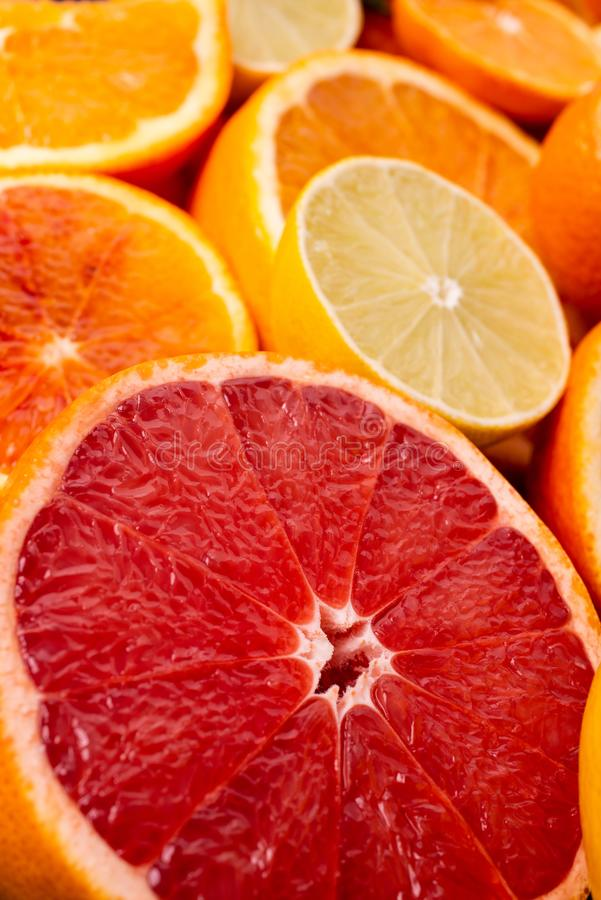 In the foreground half of red grapefruit and mixed citrus fruit slices royalty free stock image
