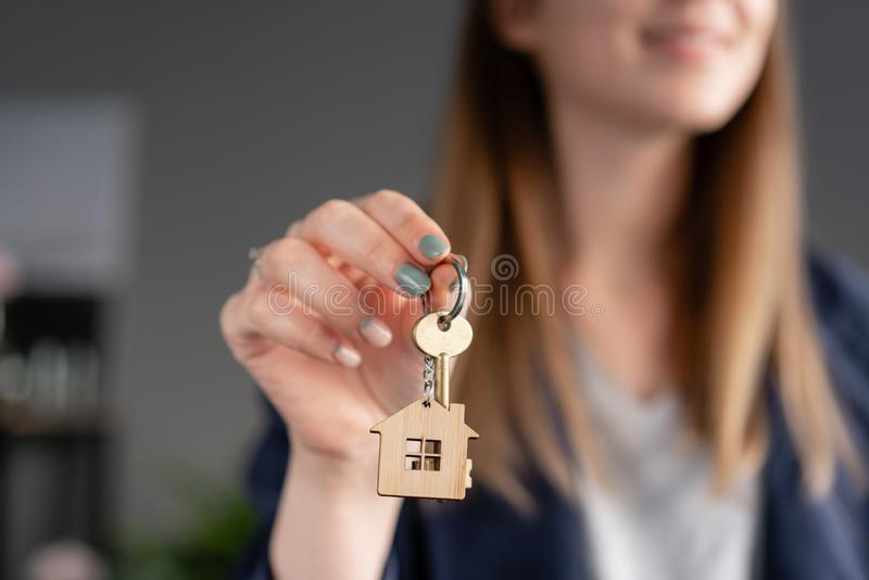 In the foreground house key in womans hands. Young pretty woman. Modern light lobby interior. Real estate, hypothec royalty free stock photography