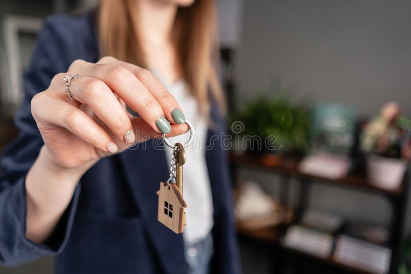 In the foreground house key in womans hands. Young pretty woman. Modern light lobby interior. Real estate, hypothec stock images