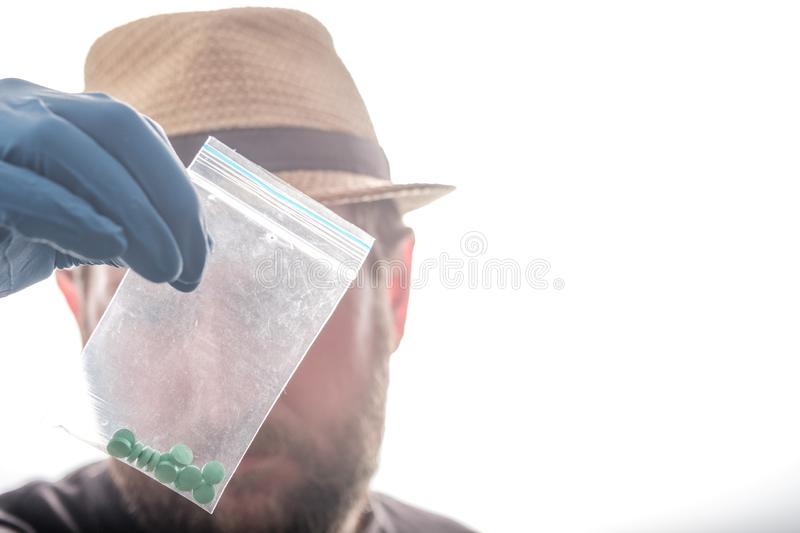 In the foreground, a man examines a package of green pills the background is white royalty free stock photo