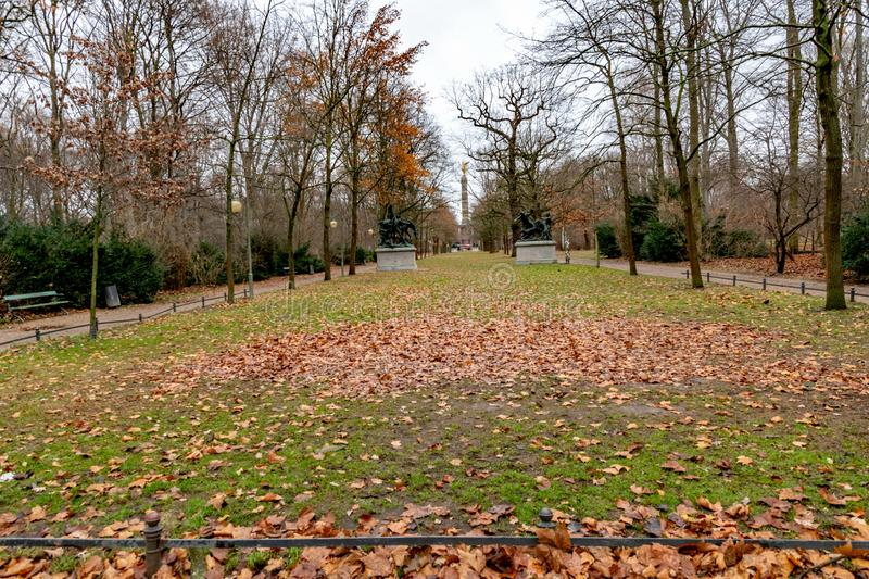 Foreground with metal fencing of green grass lawn covered with dry orange leaves. Tiergarten park of Berlin Germany. Tranquil landscape with nobody in autumn royalty free stock image
