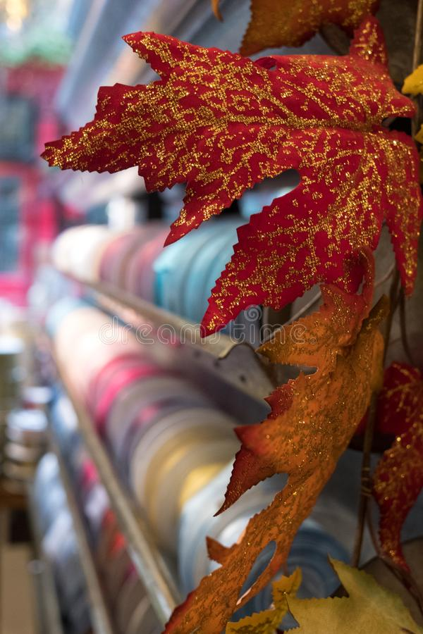 In foreground red leaves with gold glitter for Christmas. In background, reels of ribbon. Photographed at VV Rouleaux famous haberdashery shop, Marylebone Lane stock photography