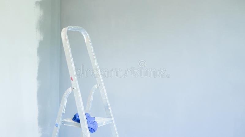 foreground stepladder. installation of an office air conditioner. Worker drilling a hole for connecting indoor and outdoor units. stock photo