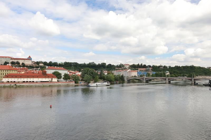 Striking view from the Charles Bridge to the Vltava river, old architecture and modernity stock photography