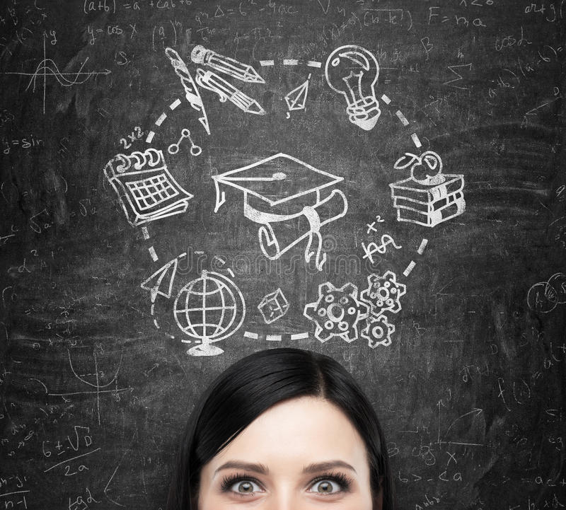 A forehead of the lady who thinks about studying and graduation. Educational icons are drawn on the black chalkboard. A forehead of the brunette lady who thinks royalty free stock image
