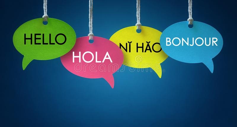 Foreign language communication speech bubbles. Foreign language colorful communication speech bubbles hanging from a cord over blue background stock photos
