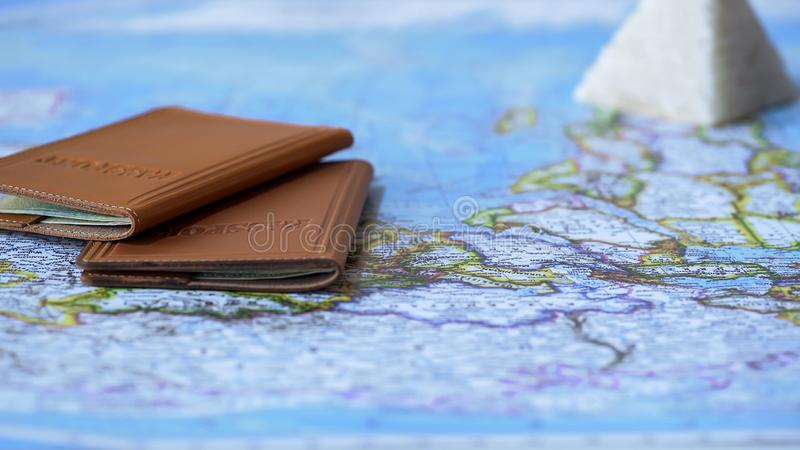 Foreign passports and souvenirs from Egypt on map, summer vacation, tour for two stock photo