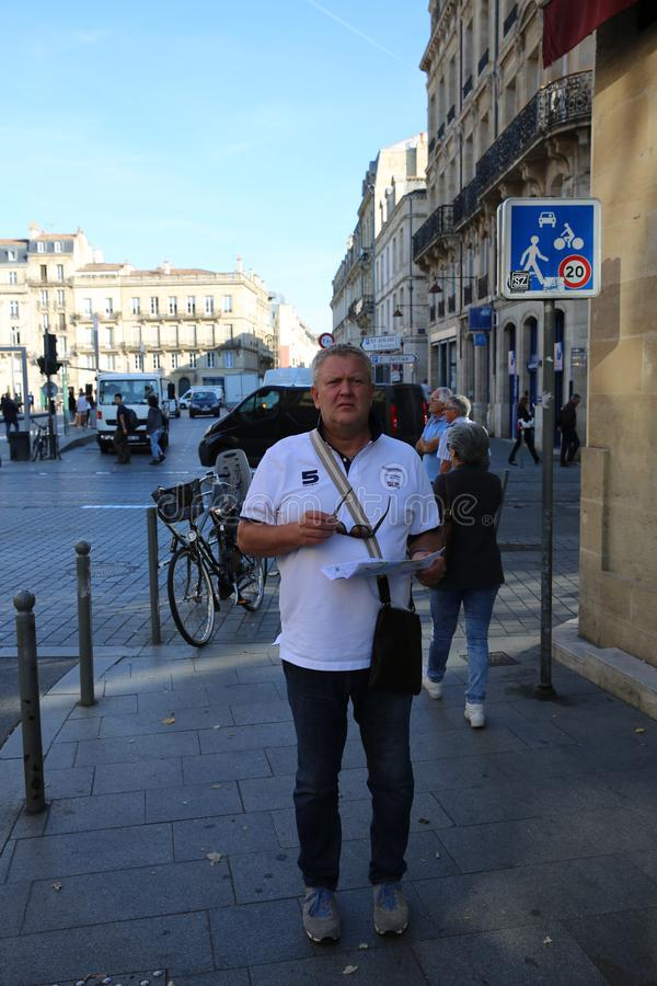 A foreign tourist completely lost in the city center of Bordeaux,. France with tourist map in hand stock image