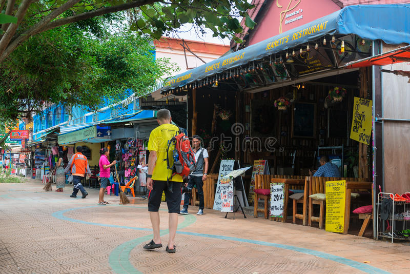 Foreign tourist strolling past Jeanett's Restaurant in Krabi, Th. KRABI, THAILAND - 15 OCT 2014: Foreign tourist strolling past a restaurant on a tourist street stock photo