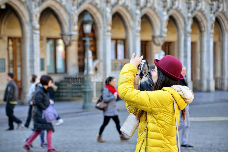 Foreign tourist takes pictures on Grand Place in Brussels. BRUSSELS, BELGIUM - MARCH 13, 2015: Foreign tourist takes pictures on Grand Place in Brussels. Cold stock photography