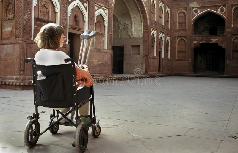 Foreign Tourist visiting Indian fort. A handicapped foreign tourist on a wheel chair looking at the fort, India royalty free stock photos