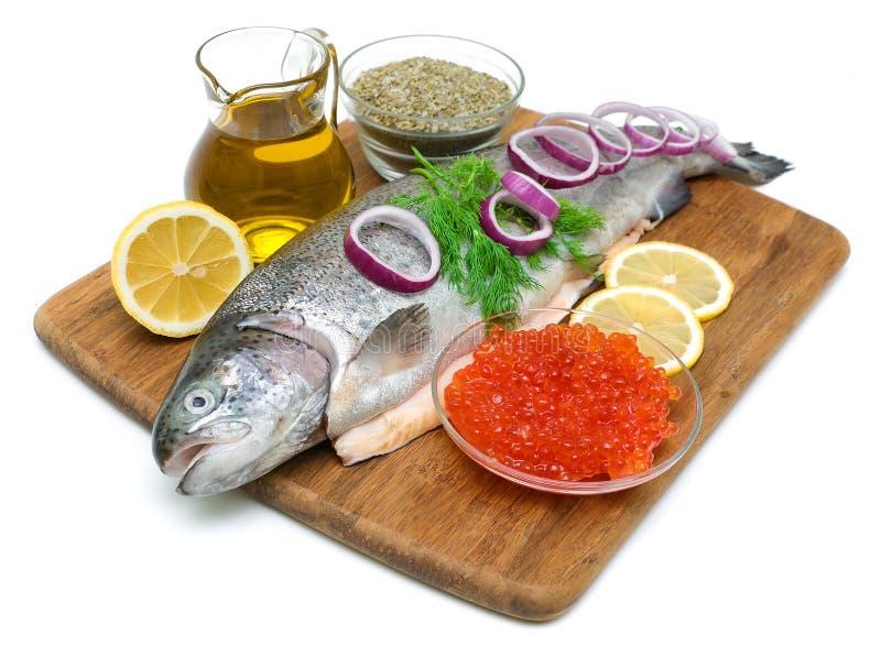 Forel, groenten, kruiden en rode kaviaar op witte achtergrond stock afbeelding