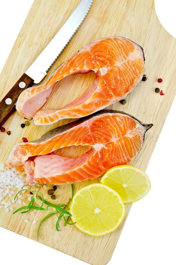 Forel met citroen en mes op plank stock afbeeldingen