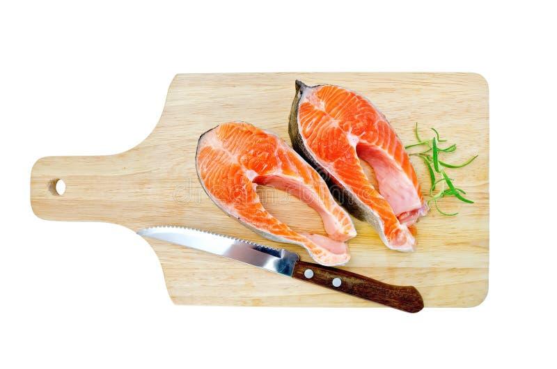 Forel op de raad met een mes en een rozemarijn stock afbeeldingen