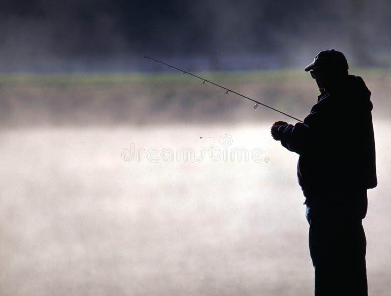 Forelle-Fischer durch einen nebelhaften See stockbild