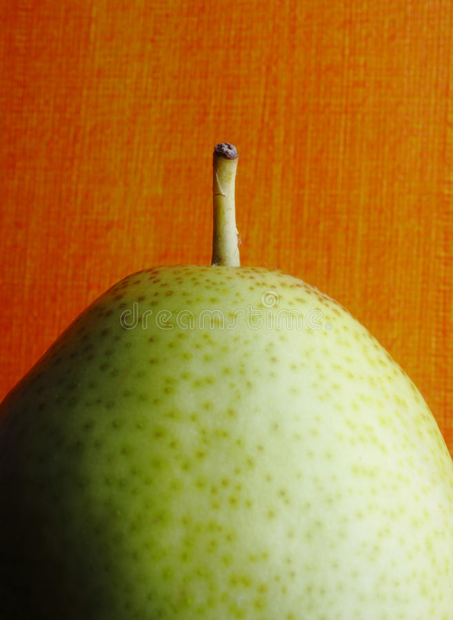 Forelle Pear against orange background royalty free stock photography