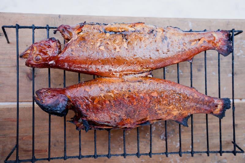 Forellen auf gebackener Forelle Holzkohle bbq grillwhole grillten auf hölzernen alten Brettern stockfotos