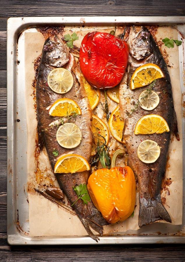 Forelvissen die met groenten en kruiden worden gebakken stock foto's
