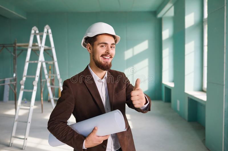 Foreman bearded man in a white helmet in a room at a construction site royalty free stock image