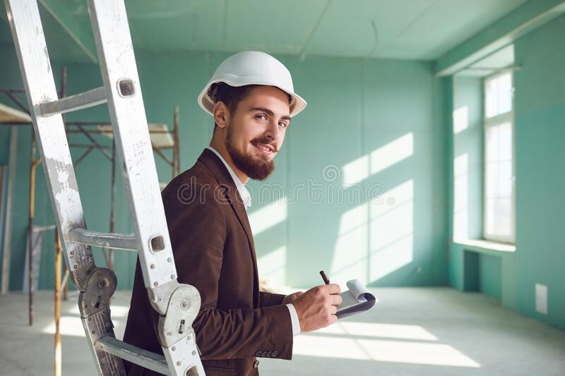 Foreman bearded man in a white helmet in a room at a construction site royalty free stock images