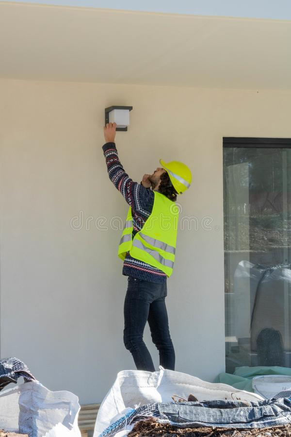 Foreman checking the installation of exterior lighting on a building under construction, site visit. Construction site house, construction site visit royalty free stock photo