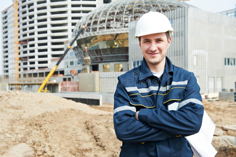 Foreman at construction site with working drawings royalty free stock photography