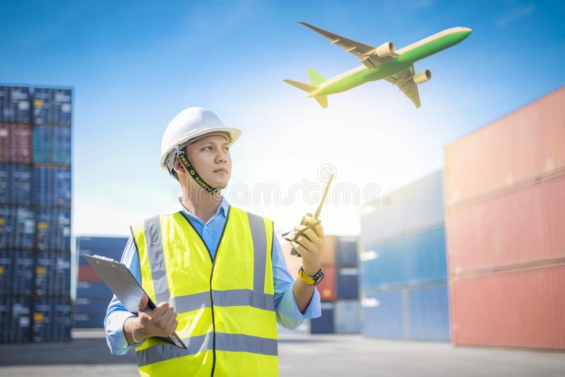 Foreman control loading containers box from cargo freight ship for import export, Foreman control industrial container cargo royalty free stock image