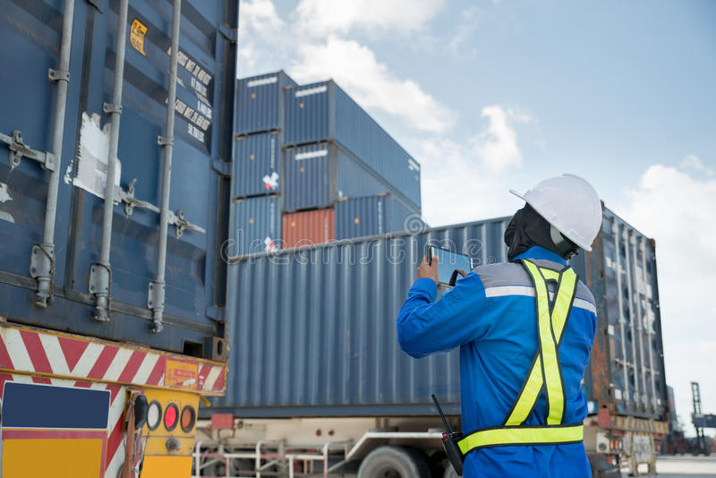 Foreman control loading Containers box from Cargo freight truck stock photography