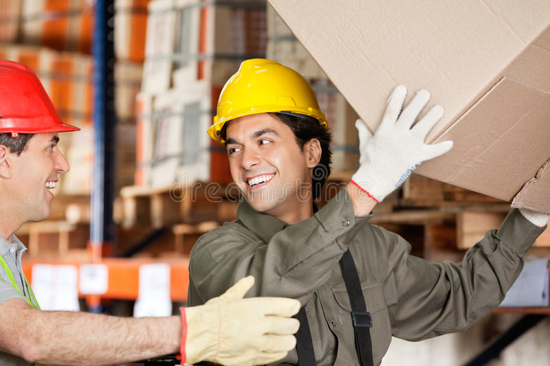 Foreman With Coworker Lifting Cardboard Box At