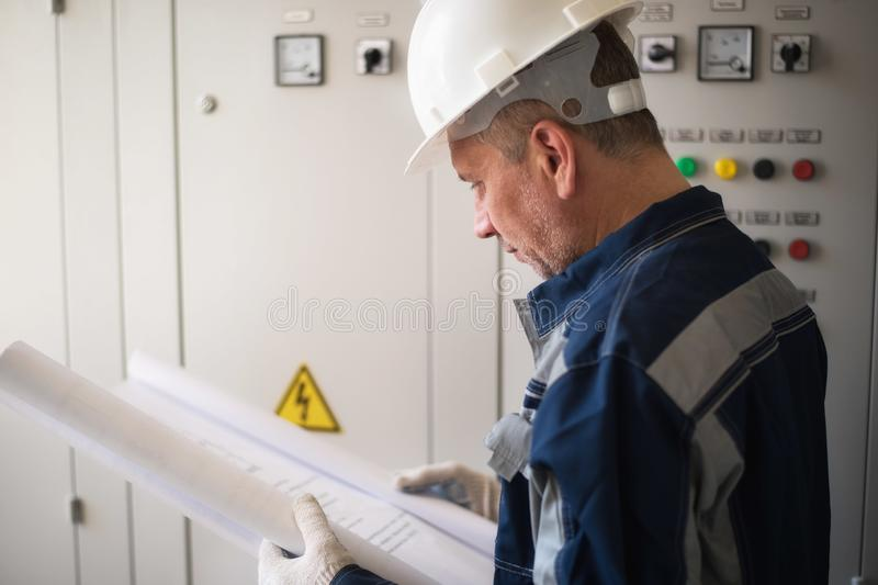 Foreman electrician examines the working draft next to the dashboard. Energy and electrical safety stock photo