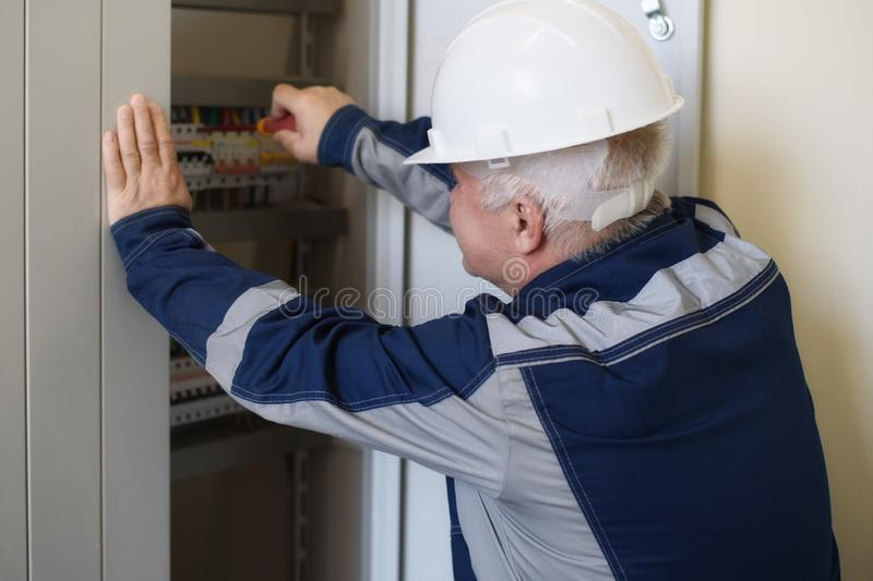 Foreman electrician next to the dashboard. Energy and electrical safety stock photography