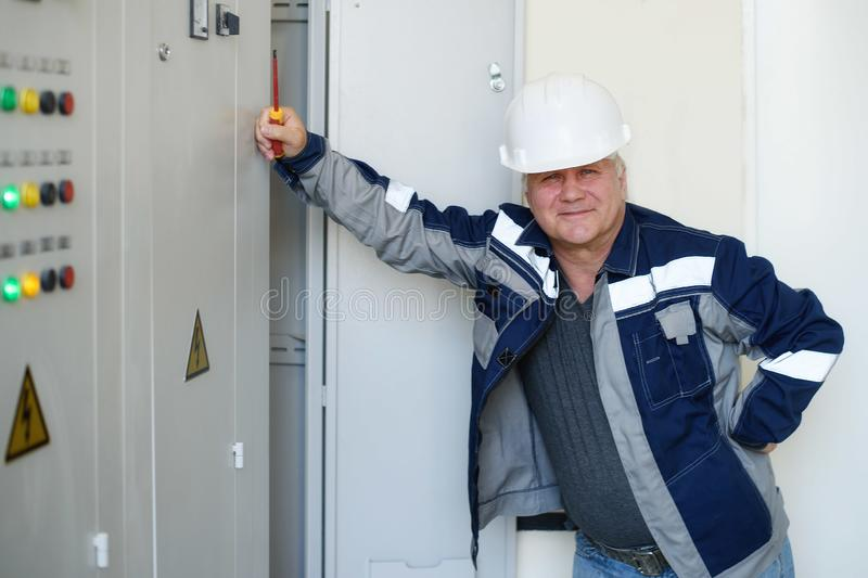 Foreman electrician next to the dashboard. Energy and electrical safety royalty free stock image